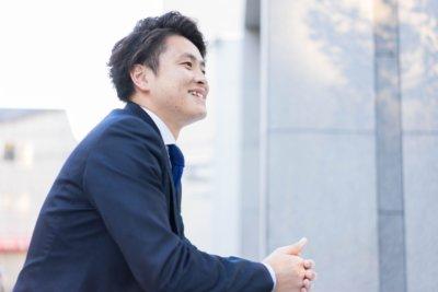 スーツで会社前に座り微笑む学生