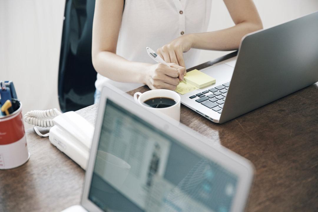 女性がパソコンの前で紙に書いている